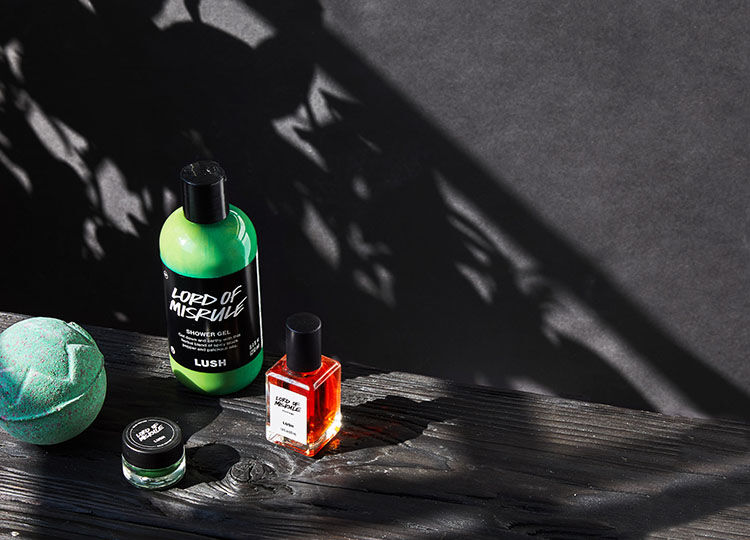 The Lord of Misrule collection: bath bomb, shower gel, liquid perfume and solid perfume are set on a dark wood table and somber shadow covers them