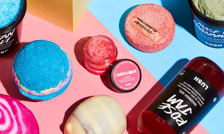 lush's bestselling bath and shower products laid out on a pink and blue surface
