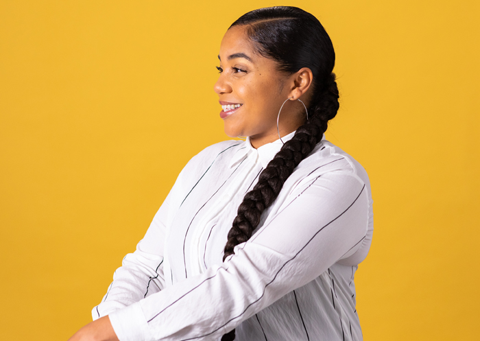 Sarah Sango poses for a photo on a yellow background and wears her hair in a long side braid.