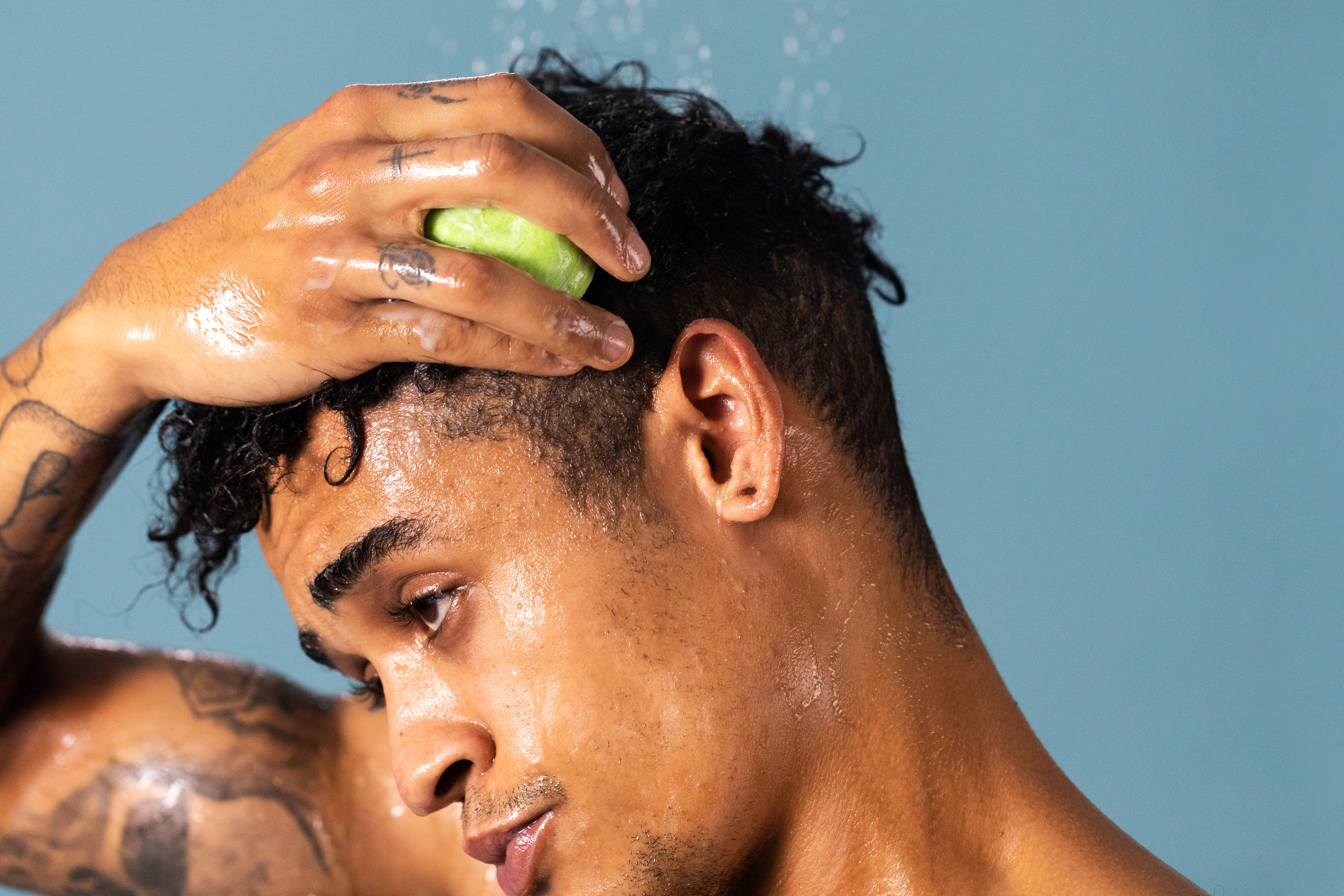 A person applies Jungle Pressed Conditioner to their hair.