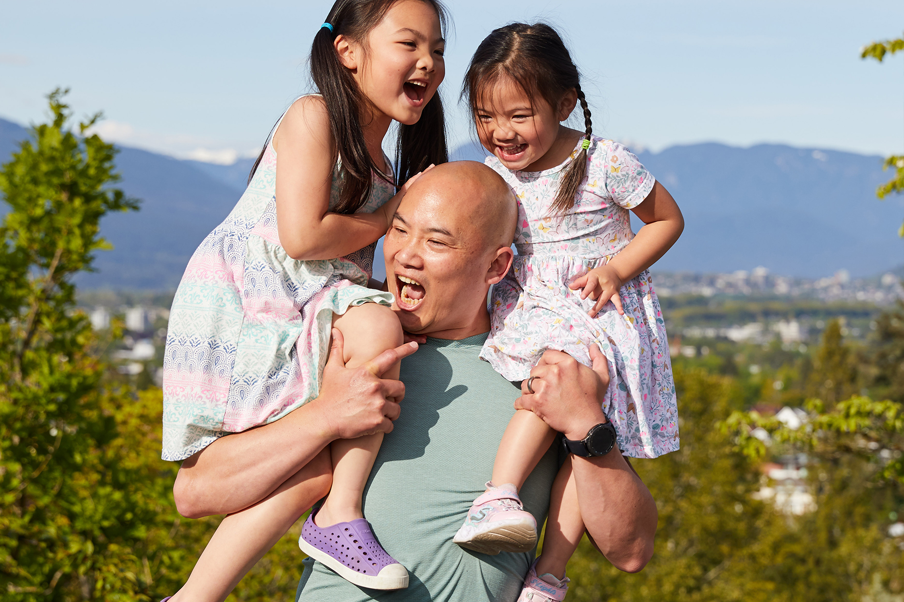 Alfred carries his two daughters on his shoulders as he plays with them in a park.