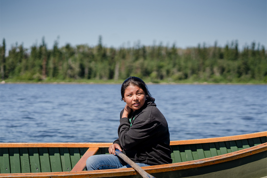 A person sits in a canoe wearing a dark shirt and jeans against a backdrop of a boreal forest line and blue lake water.
