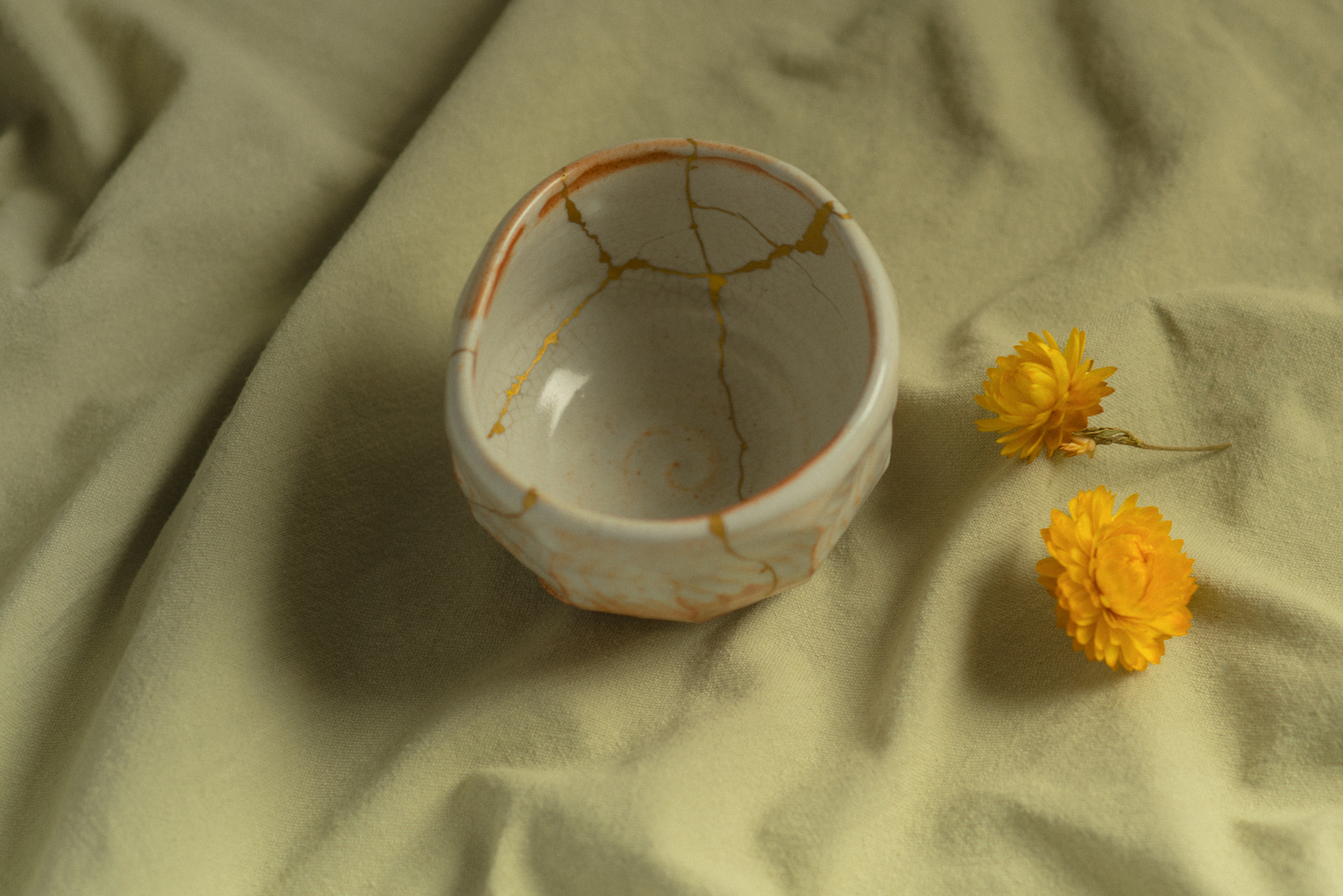 A bowl with cracks filled in with gold sits on a canvas sheet beside a yellow flower.