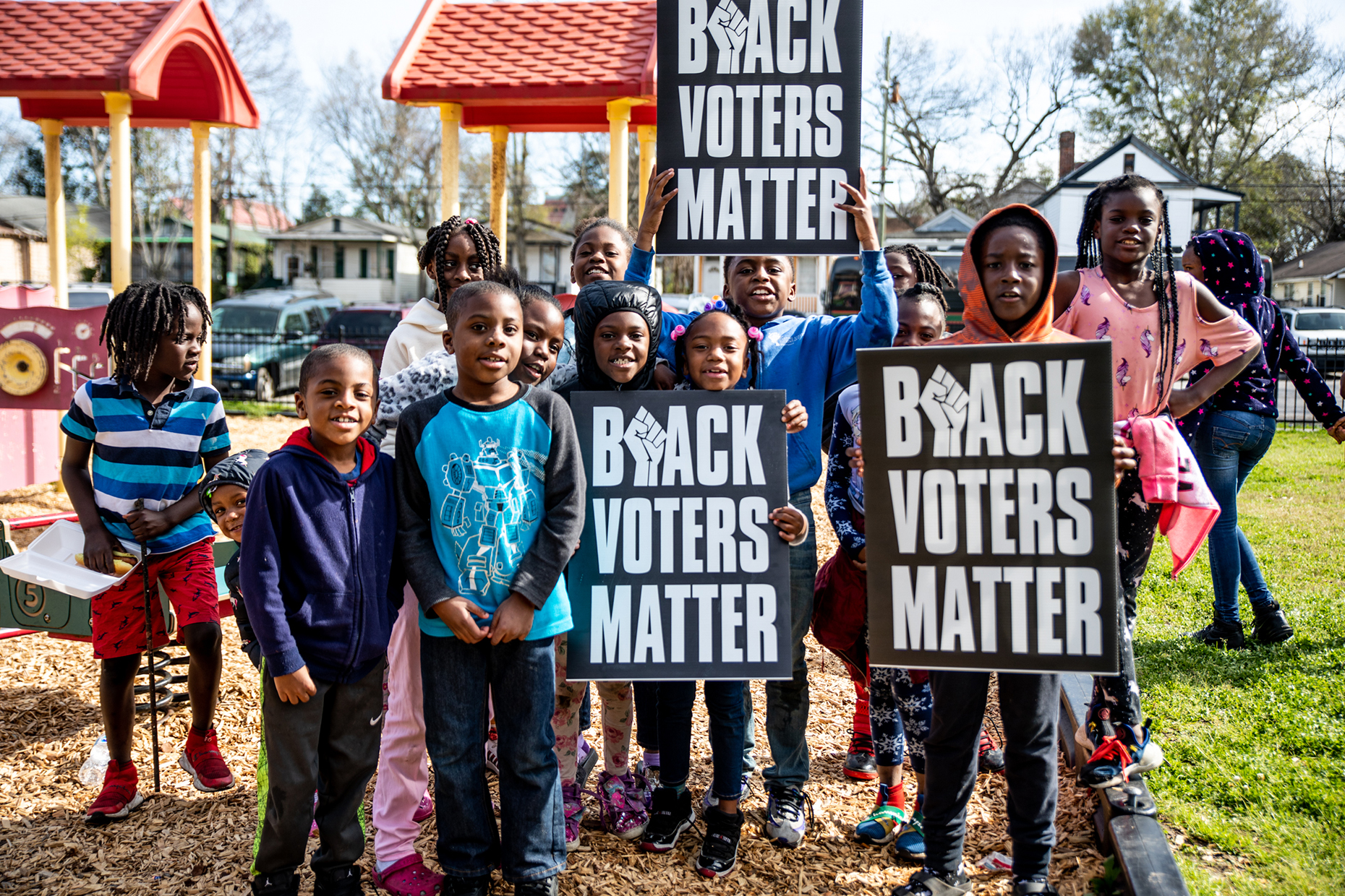 Black kids in a playground holding signs that say 'Black voters matter'.