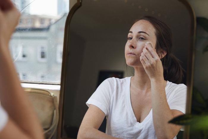 Une personne masse une huile pour le visage nue sur sa peau.