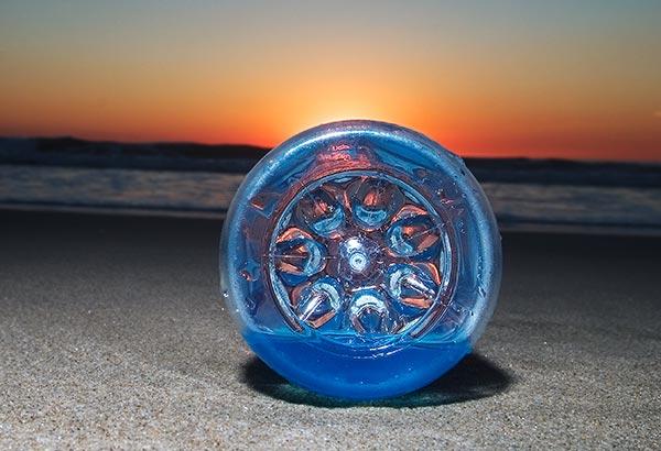 A plastic bottle pollutes a beach