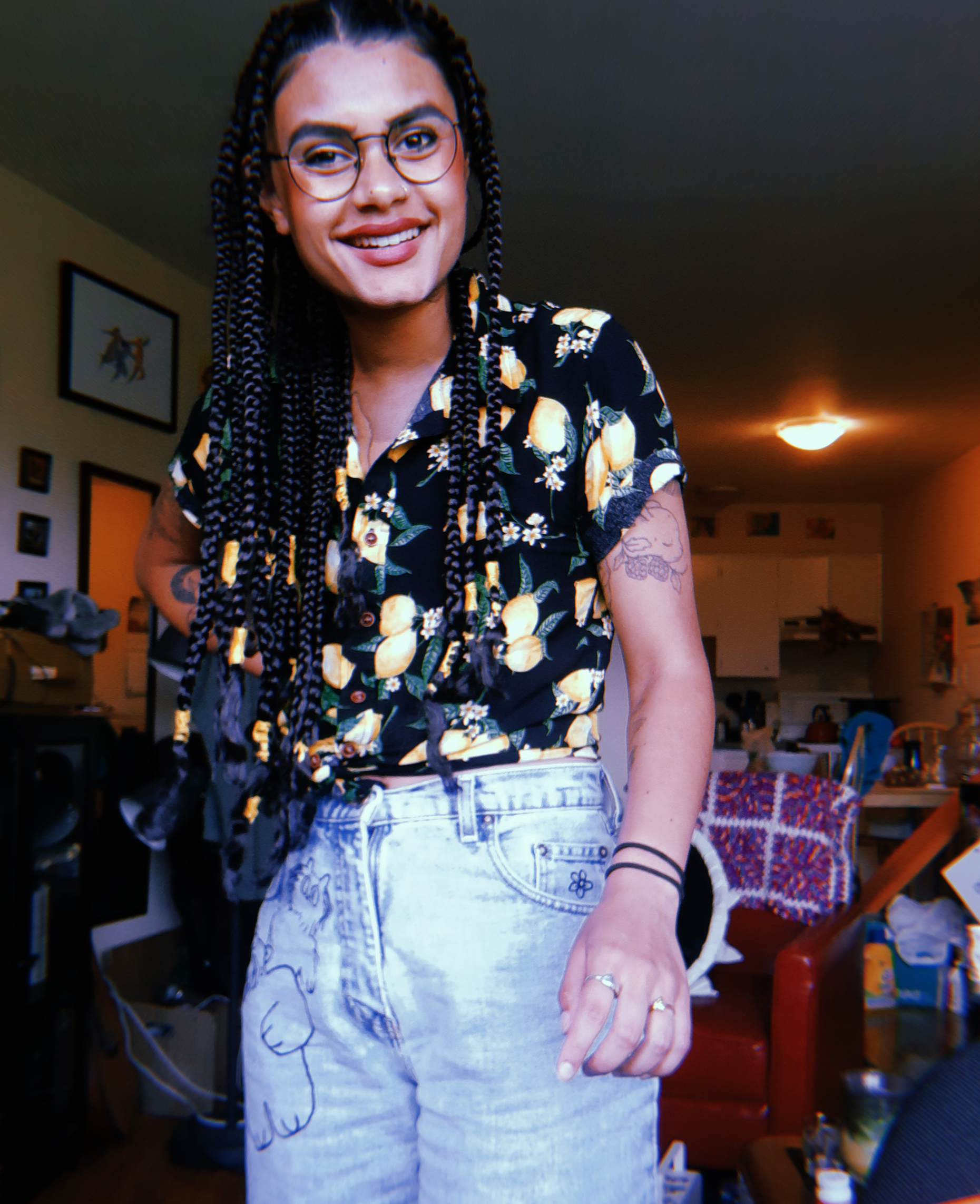 A picture of Zion Bull smiling and standing up in front of the camera, wearing jeans and a colorful blouse.