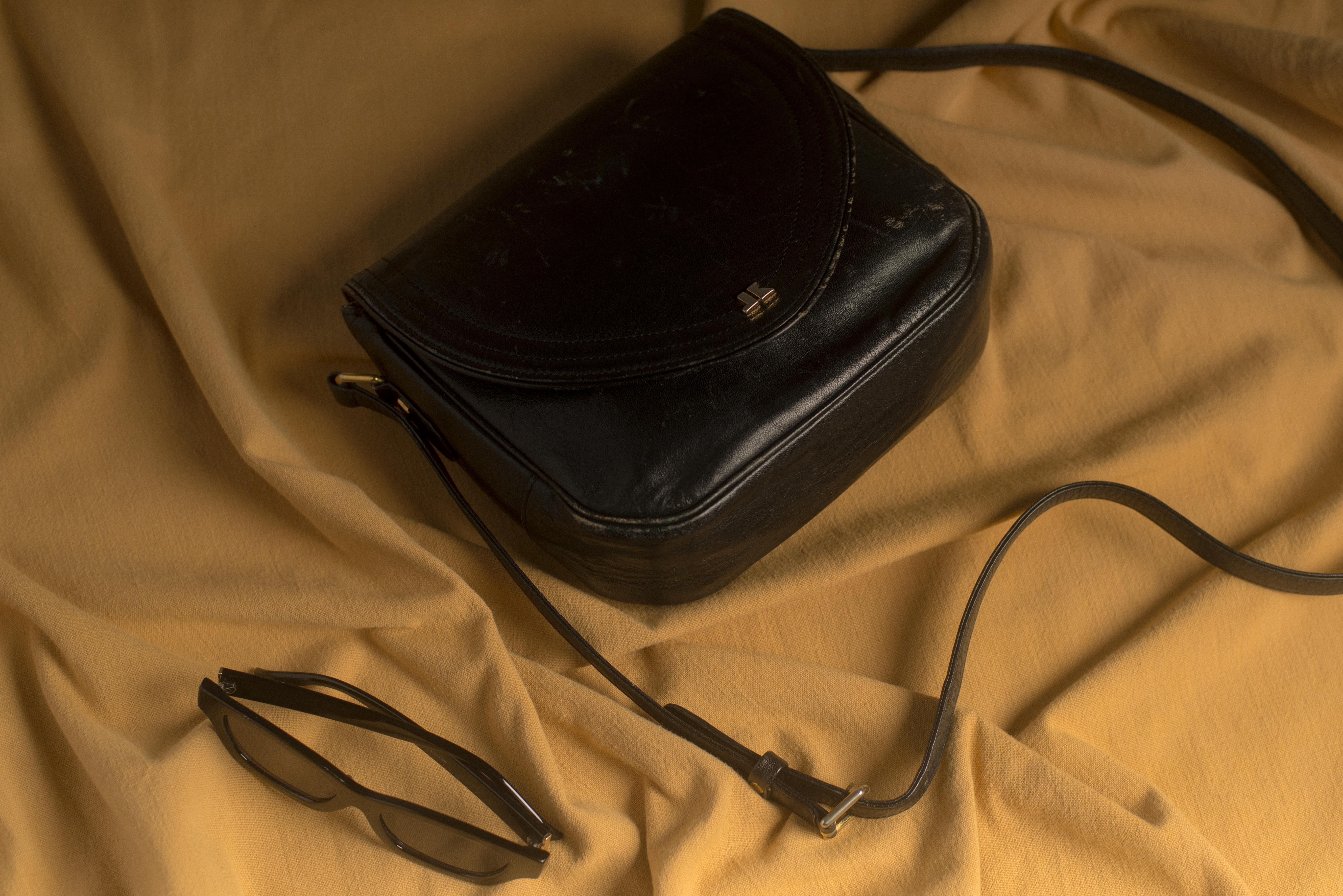 A black handbag sits against a canvas cloth with a pair of black sunglasses.