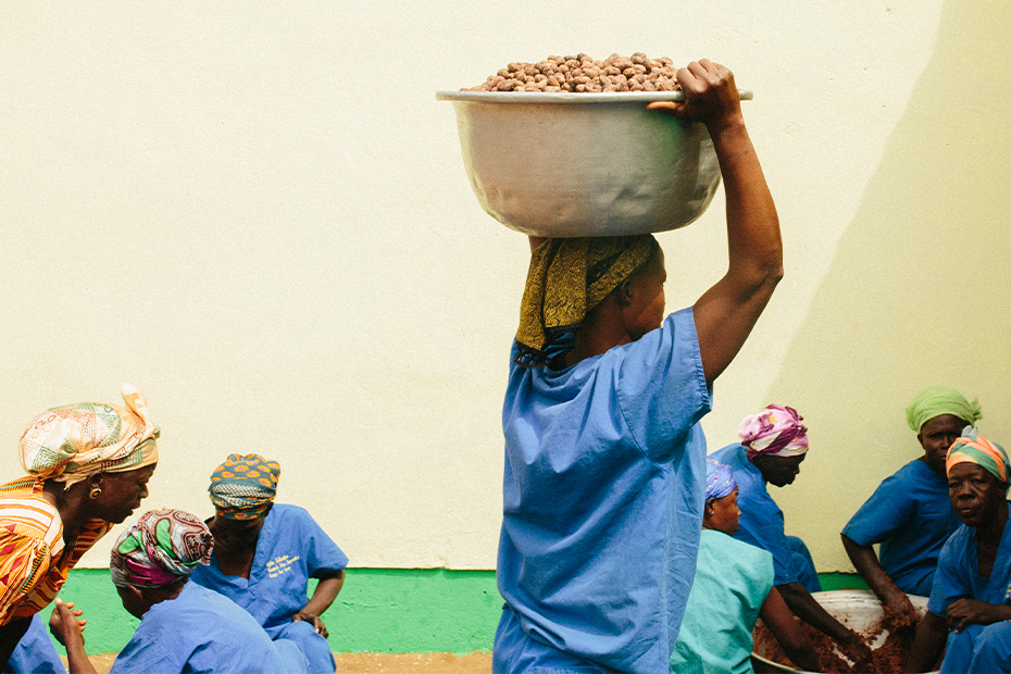 A woman carries a bin of shea nuts on her head as other women work in the background.