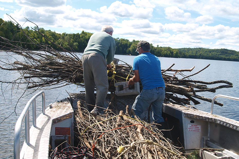 Two people stand on a boat filled with tree branches.