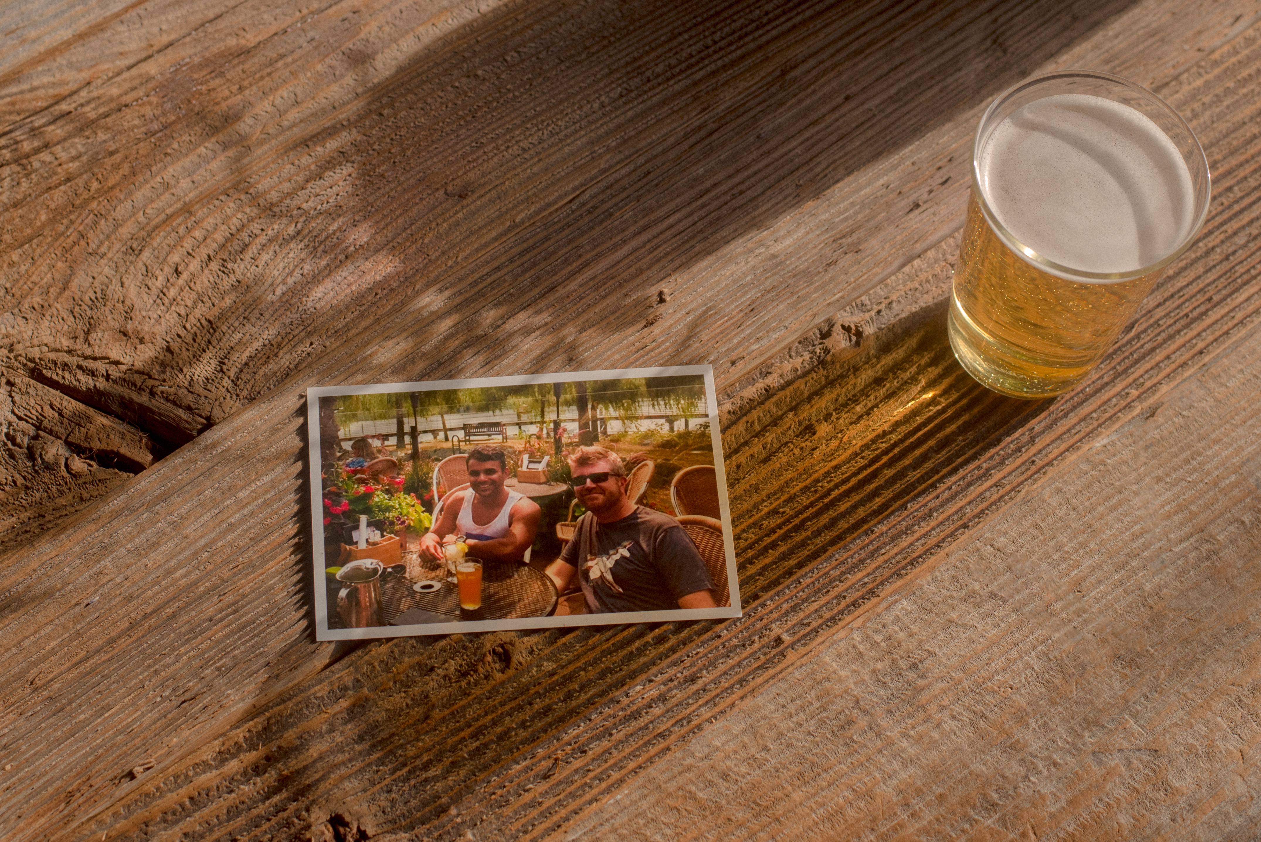 A photograph of two friends sits on a wood table beside a glass of beer.