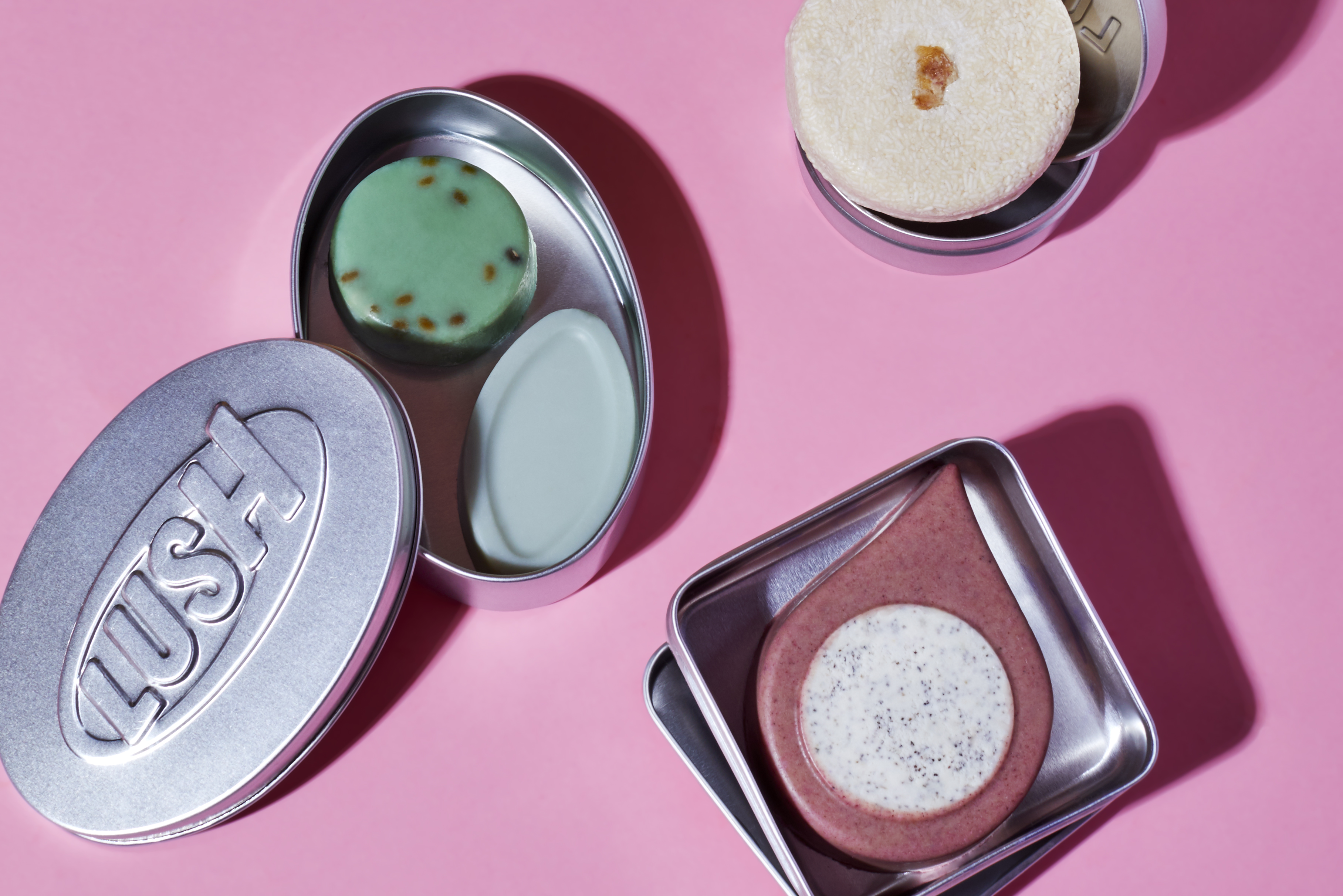 A naked shower oil, a naked cleanser, a naked facial oil and a shampoo bar are displayed in reusable metal tins.