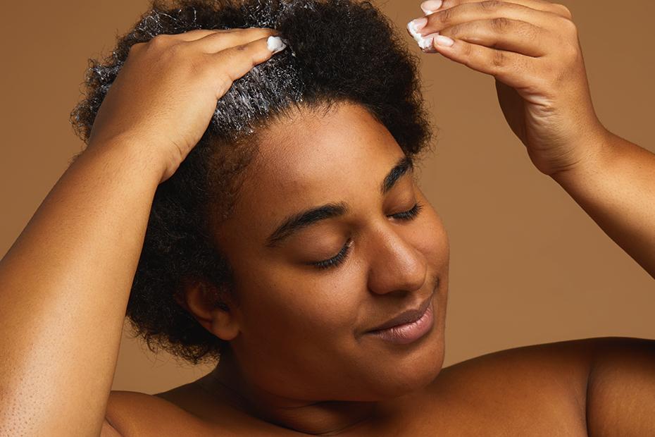 Une personne applique le traitement capillaire Roots sur ses cheveux.