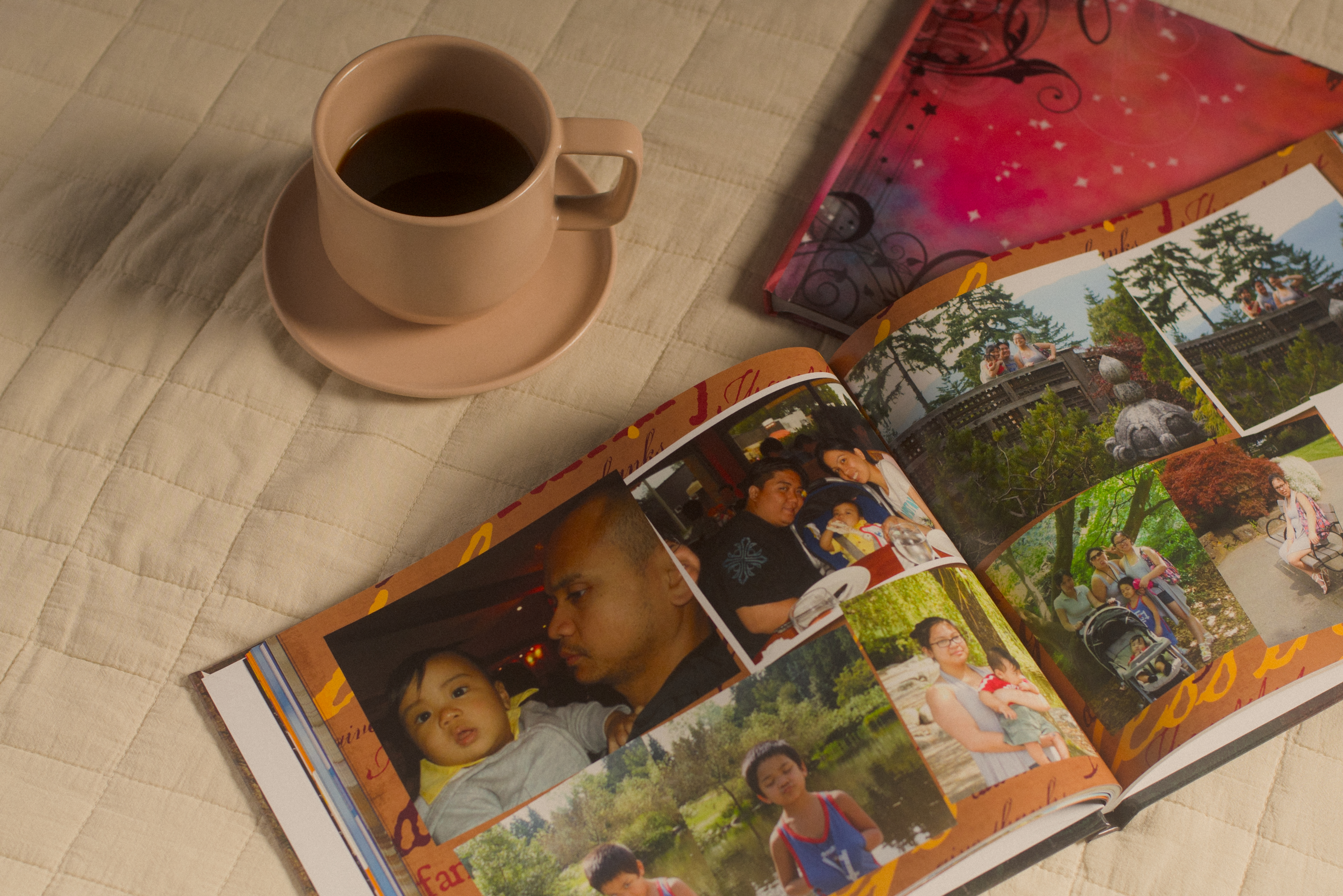 A photo album filled with old family photos sits on a tan cloth with a cup of coffee nearby.
