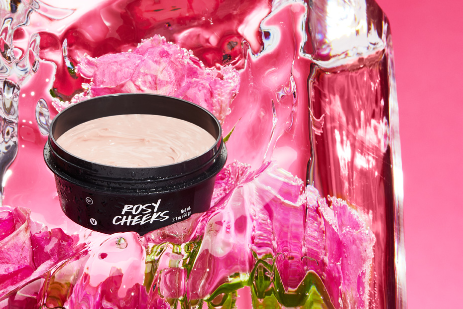 A black pot of Rosy Cheeks sits on top of melting ice against a pink background.