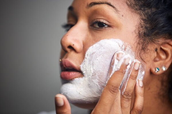 A woman applies FOMO Jelly Face Mask to her cheek.