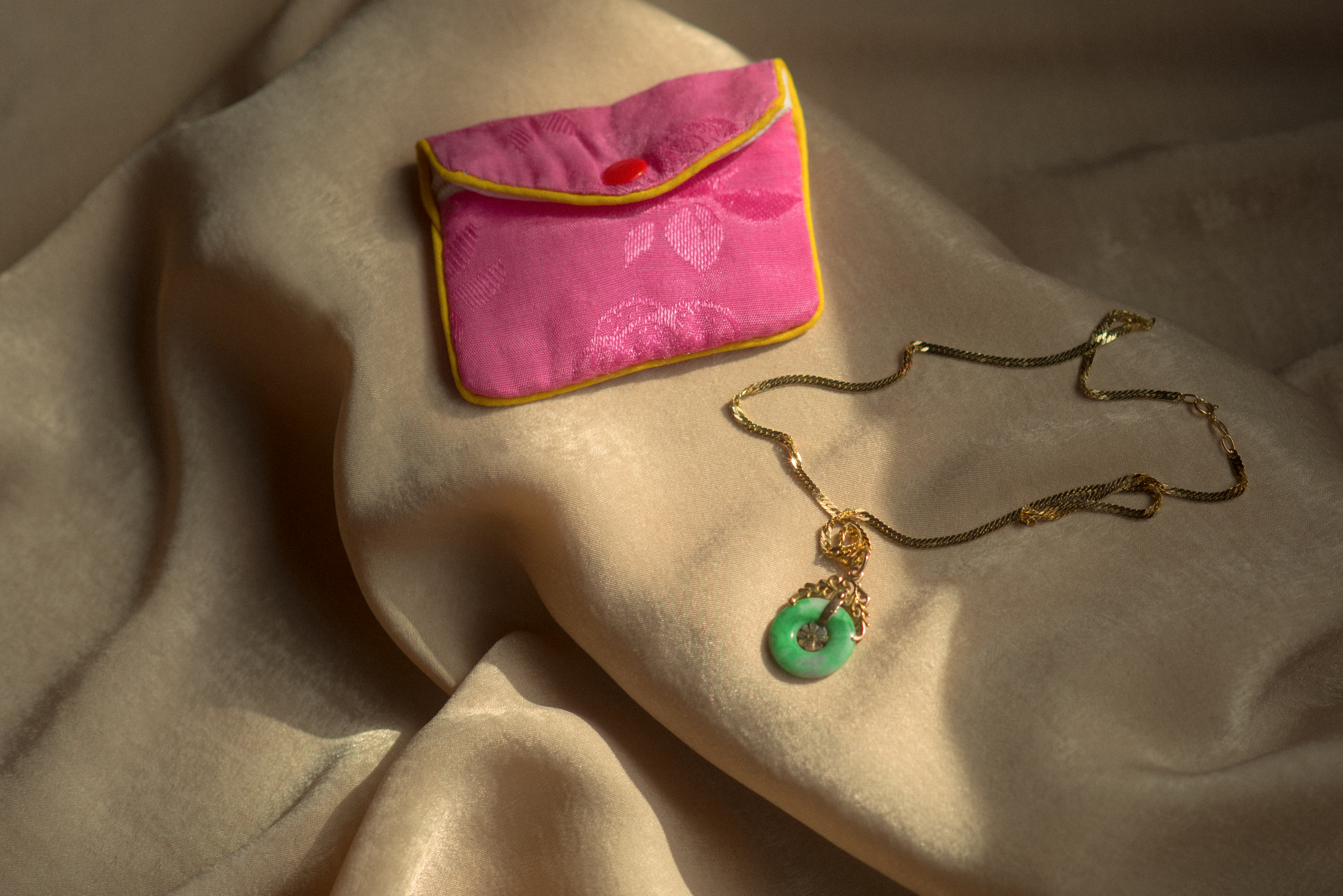 A gold necklace with a green circle pendant sits beside a pink pouch on a tan sheet.