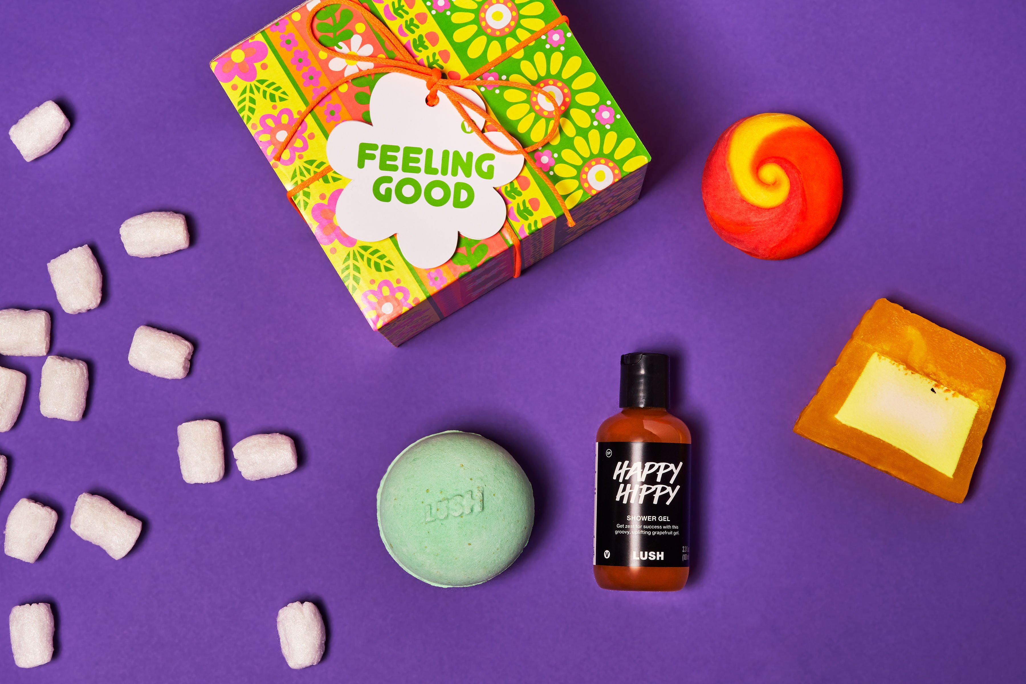 Lush Feeling Good Gift, compostable packing peanuts, Happy Hippy, Avobath, Brightside, and Lemon Zest sit against a purple background
