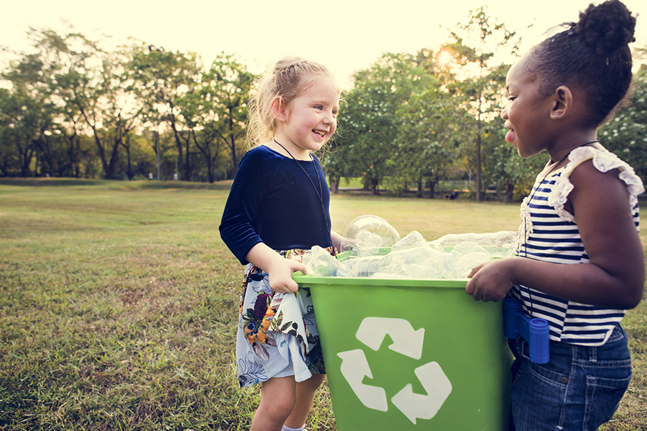Two children hold a recycling bin while standing on grass.