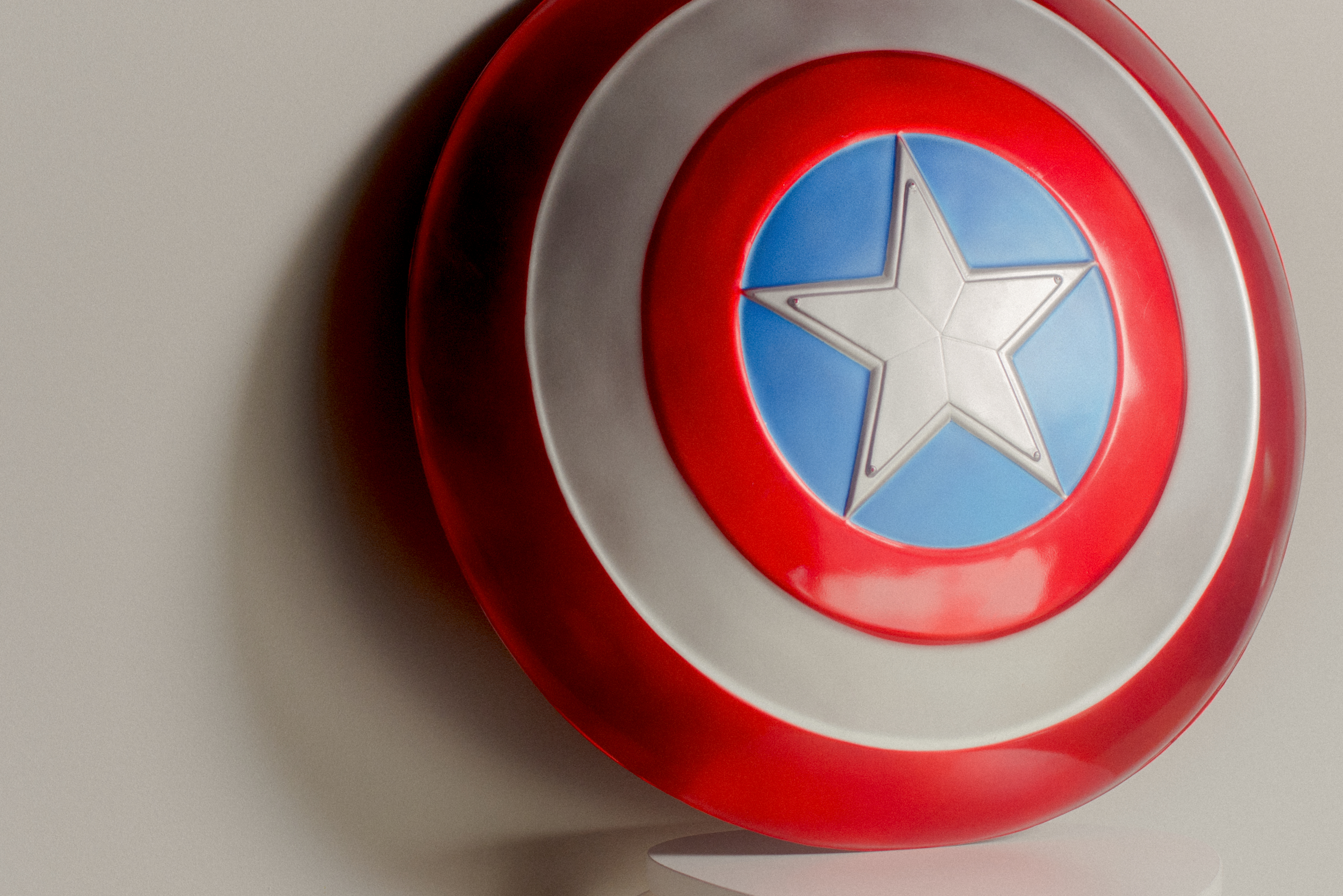 Captain America's red, white and blue shield sits perched on a stool against a white wall.