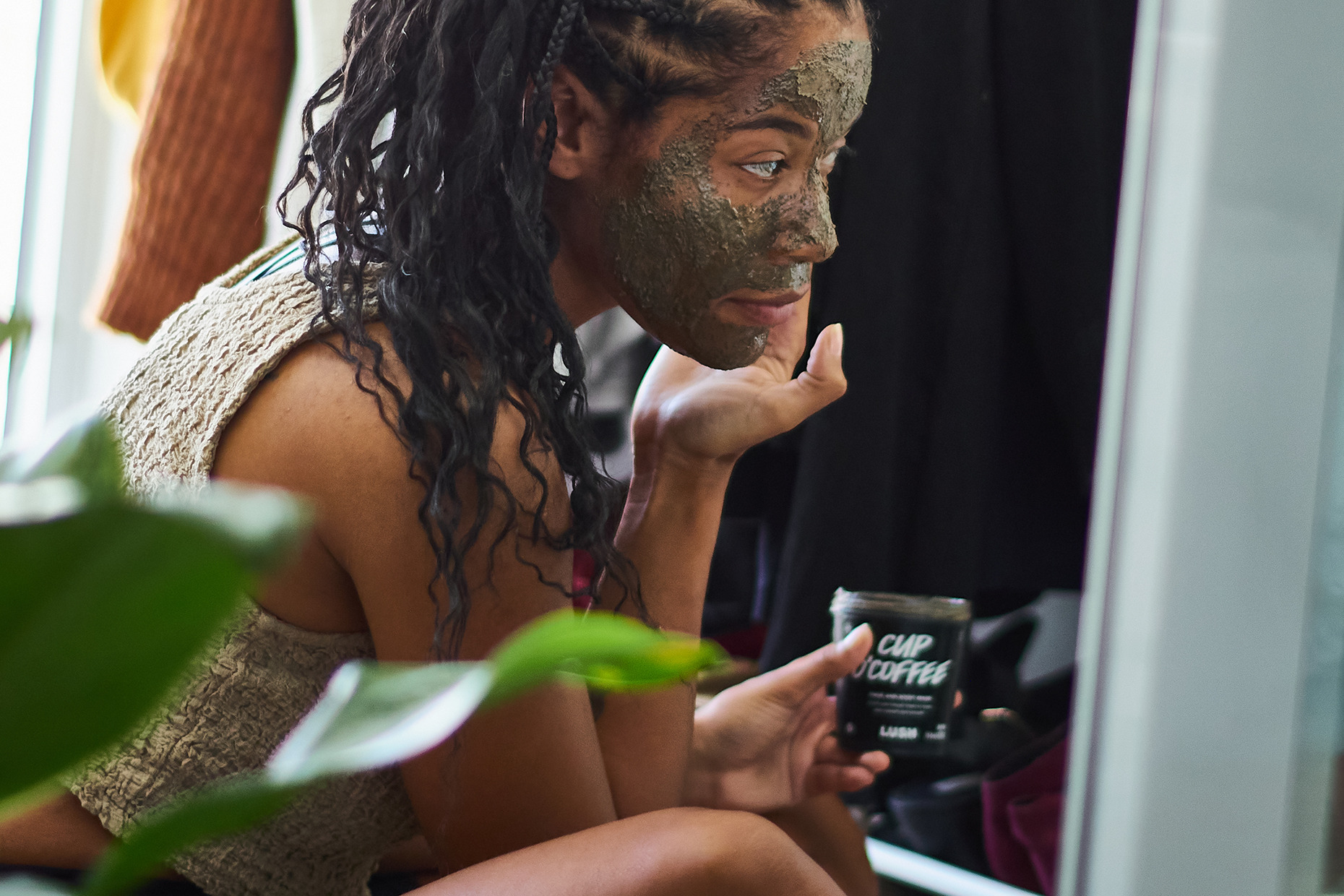 A person rubs Cup O' Coffee Face And Body Mask into their skin.