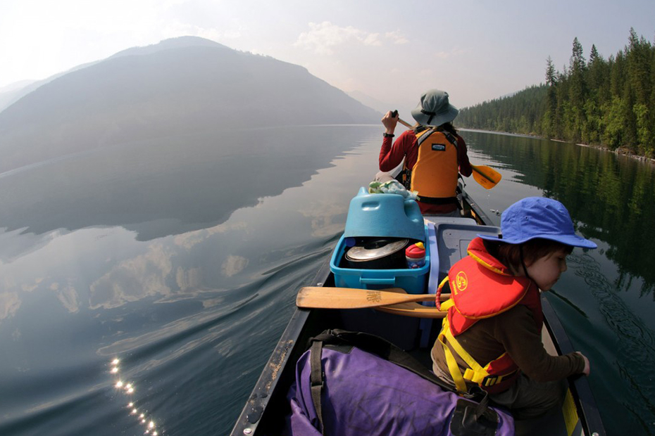 An adult and child sit in a canoe paddling along a body of water with a forest and mountain in the distance.