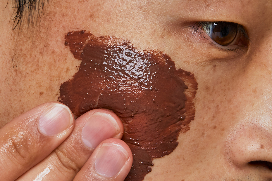 A close up on someone's face as they apply Glen Cocoa Fresh Face Mask to their cheek.