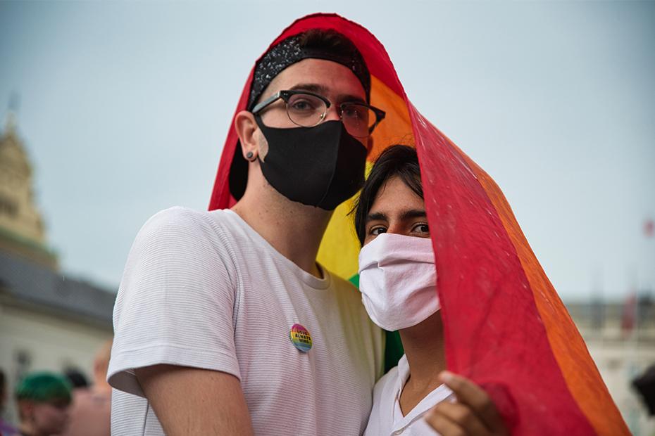 Deux personnes portant un masque et drapées d'un drapeau de la fierté se tiennent devant la caméra.